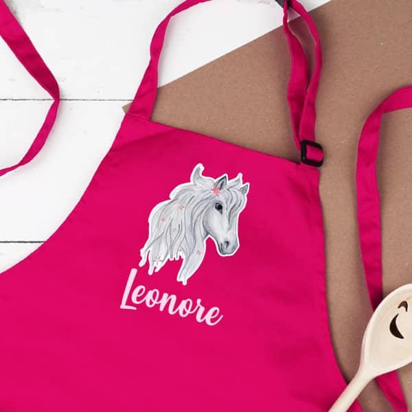 Pinkfarbene Kinderschürze mit Pferd und Name